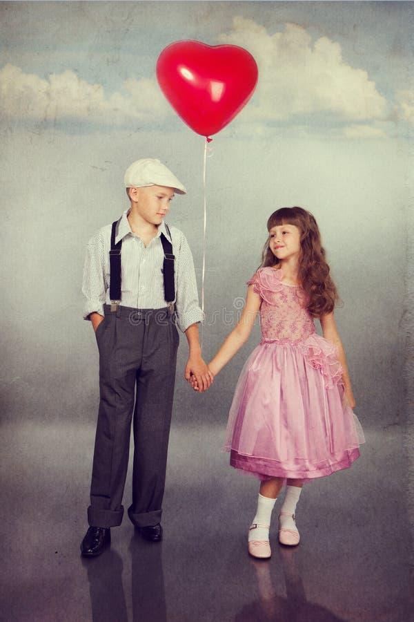 Niños lindos que caminan con un globo rojo fotos de archivo