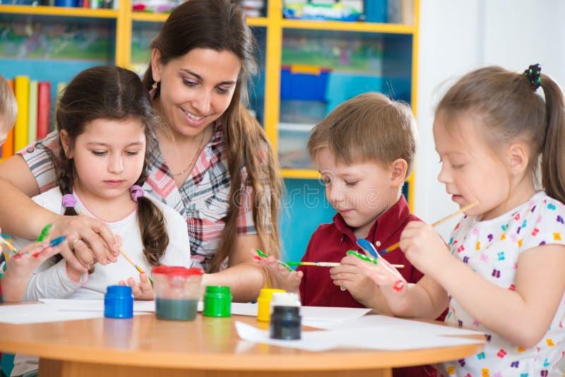 Niños lindos que dibujan con el profesor en la clase preescolar fotografía de archivo