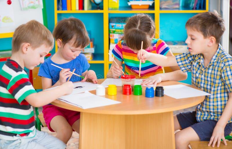 Niños lindos que dibujan con las pinturas coloridas en la guardería imagenes de archivo