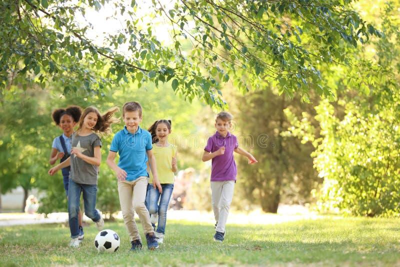 Niños lindos que juegan con la bola al aire libre el día soleado imagen de archivo libre de regalías