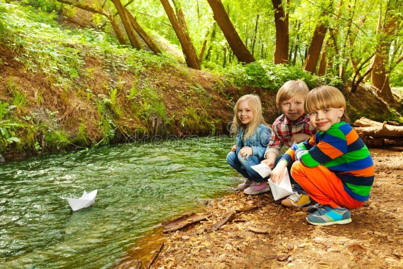 Niños lindos que juegan con las naves de papel en la orilla fotos de archivo