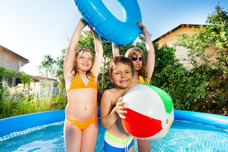 Niños lindos que juegan en piscina inflable grande afuera fotografía de archivo