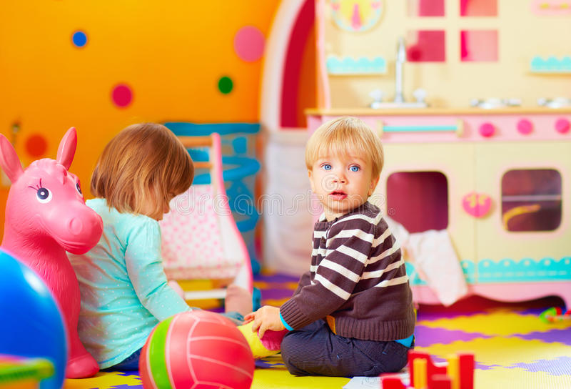 Niños lindos que juegan junto en centro de guardería fotografía de archivo libre de regalías