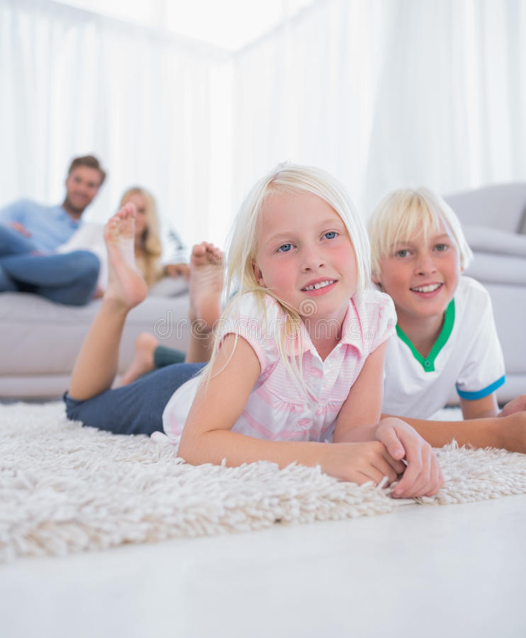 Niños lindos que mienten en la alfombra que sonríe en la cámara imágenes de archivo libres de regalías