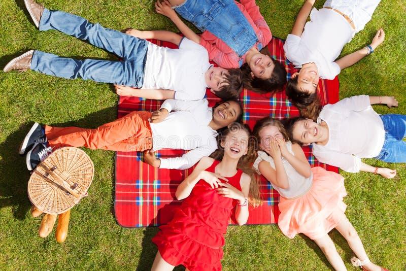 Niños lindos que ponen en un círculo en la manta de la comida campestre imagenes de archivo