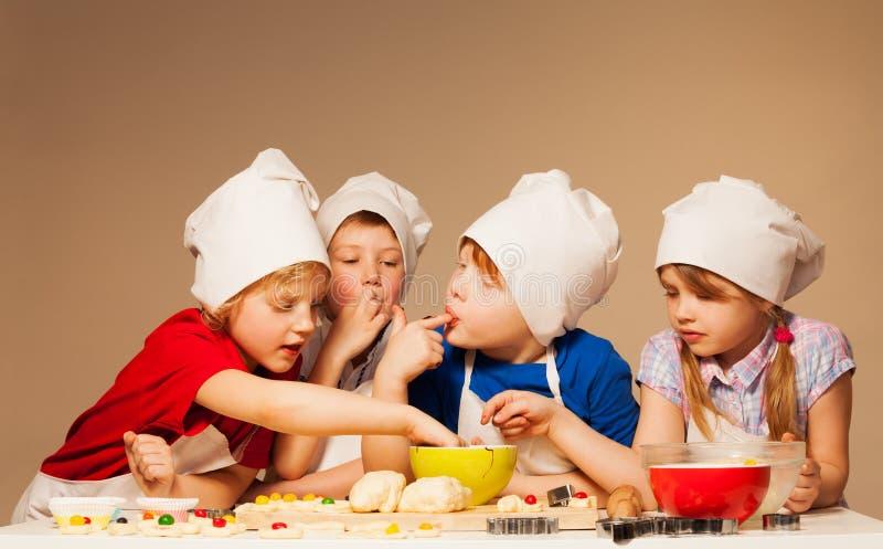 Niños lindos que prueban la pasta para las galletas hechas a mano imágenes de archivo libres de regalías
