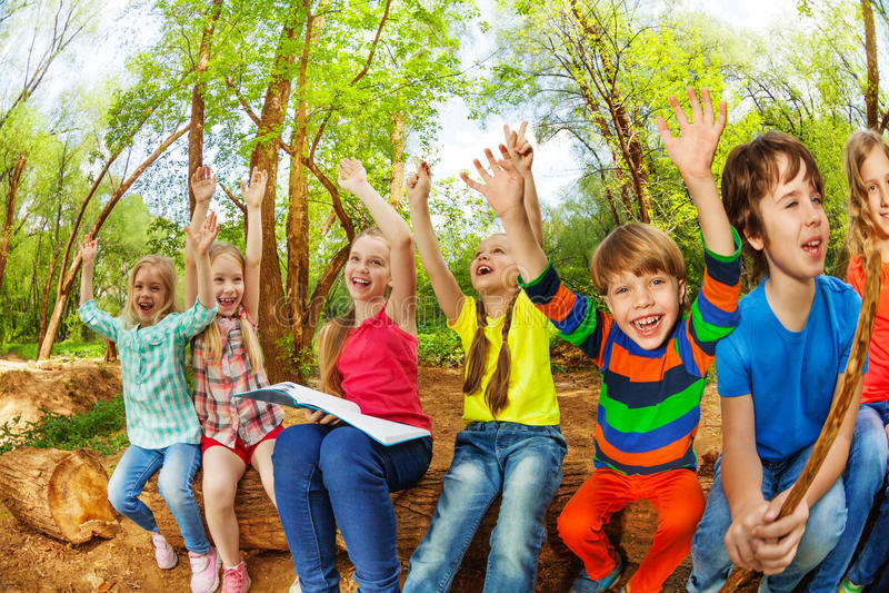 Niños lindos que se sientan en el registro con sus manos para arriba fotos de archivo libres de regalías