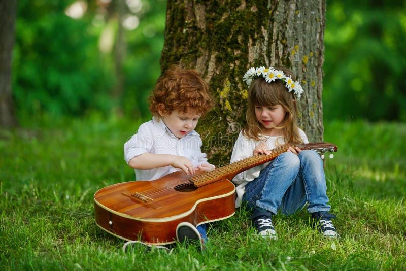 Niños lindos que tocan la guitarra foto de archivo libre de regalías