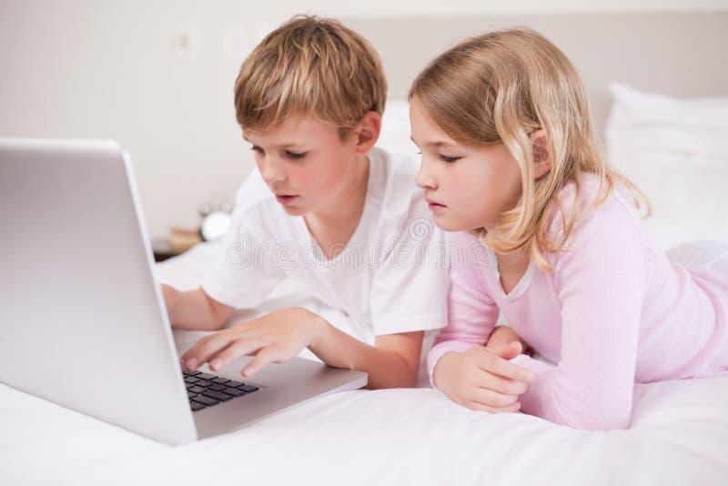 Niños lindos que usan una computadora portátil imagen de archivo libre de regalías