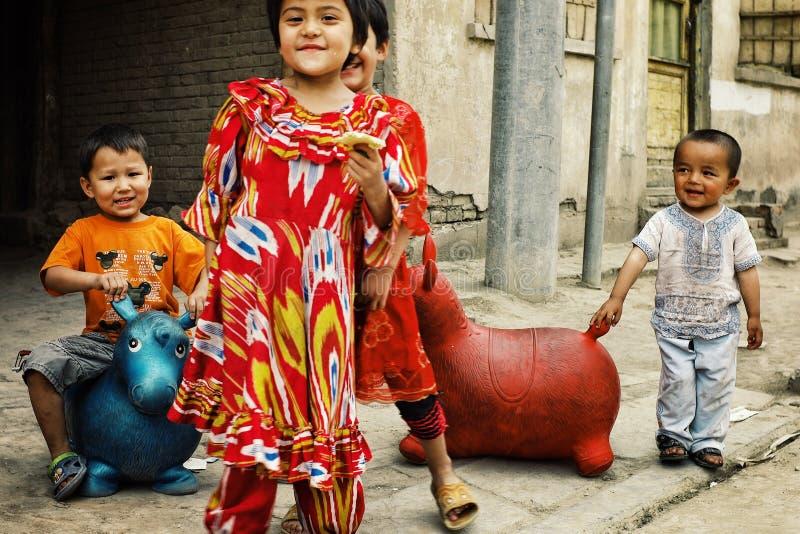 niños locales divertidos lindos que juegan con los juguetes inflables de la gorila en la calle fotos de archivo