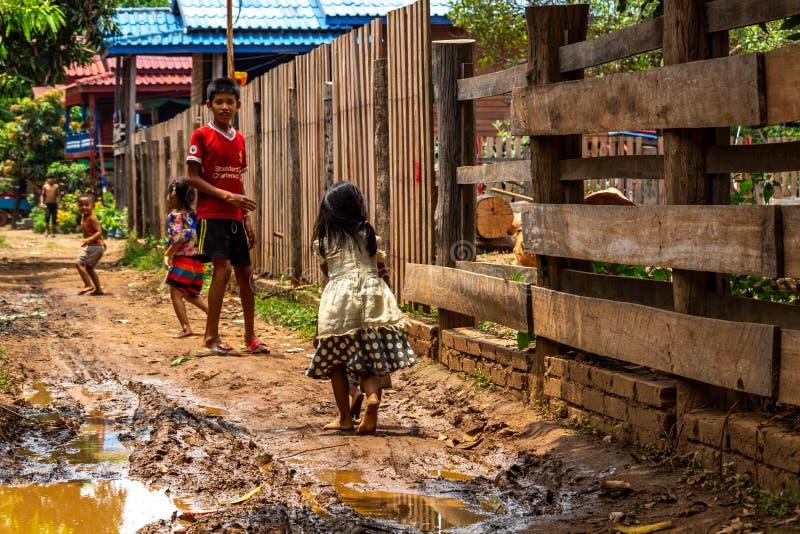 Niños locales en una trayectoria fangosa Laos imágenes de archivo libres de regalías