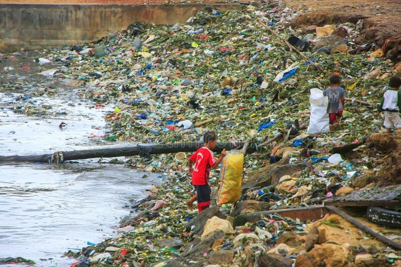 Niños locales que pasan a través de la basura en la costa de mar en Labuan Bajo fotos de archivo libres de regalías