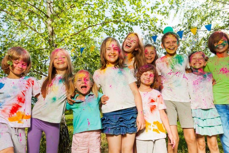 Niños manchados con el polvo coloreado que se coloca en fila fotografía de archivo