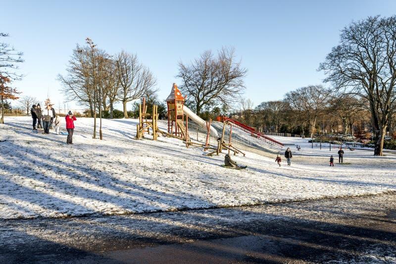 Niños montan trineos en una pequeña pendiente cubierta de nieve cerca del parque infantil en Duthie Park, Aberdeen, Escocia imagen de archivo