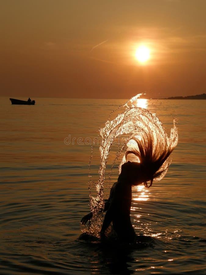 Niños, muchacha y barco en puesta del sol imagen de archivo