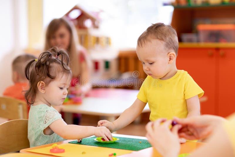 Niños muchacha y moldeado del muchacho de la pasta del juego en guardería imagen de archivo
