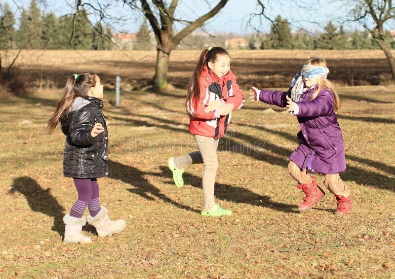 Niños - muchachas que juegan la piel de ante del hombre ciego fotos de archivo