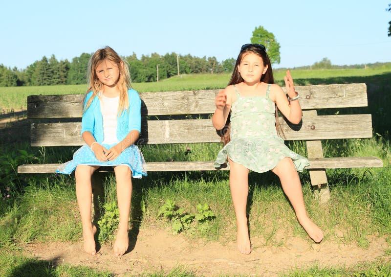 Niños - muchachas que se sientan en un banco fotos de archivo libres de regalías