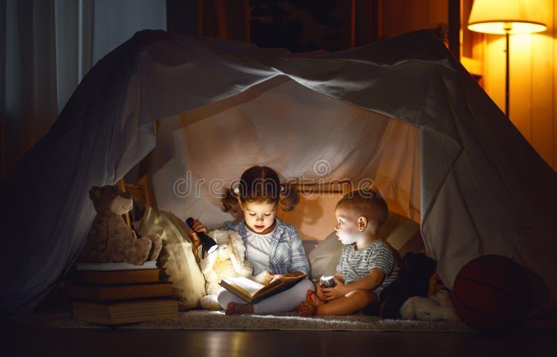 Niños muchacho y libro de lectura de la muchacha con la linterna en tienda imagen de archivo libre de regalías