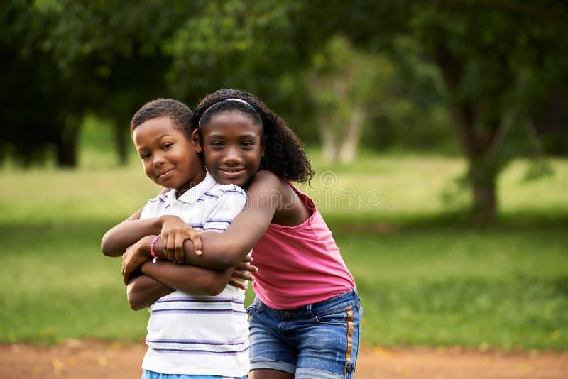 Niños muchacho y muchacha africanos en el abrazo del amor foto de archivo libre de regalías