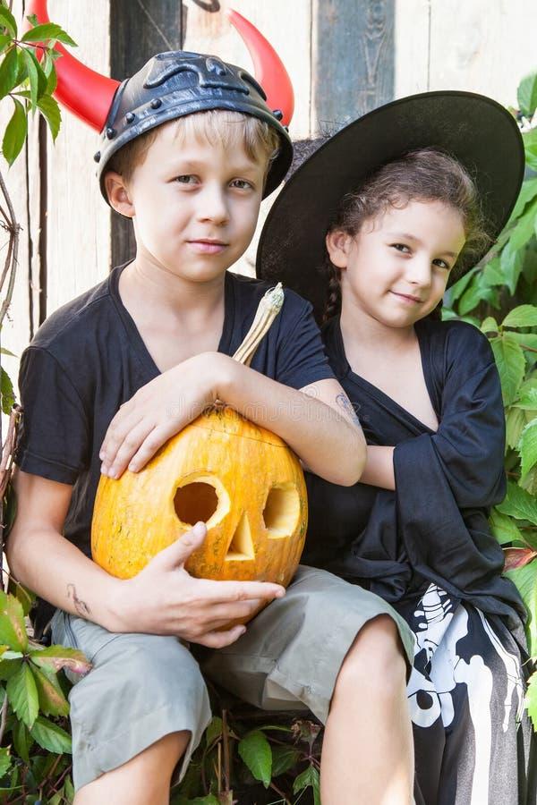 Niños muchacho y muchacha con la calabaza de Halloween fotos de archivo