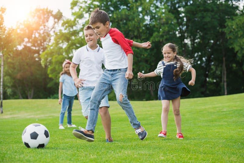 Niños multiétnicos felices que juegan a fútbol con la bola en parque foto de archivo libre de regalías