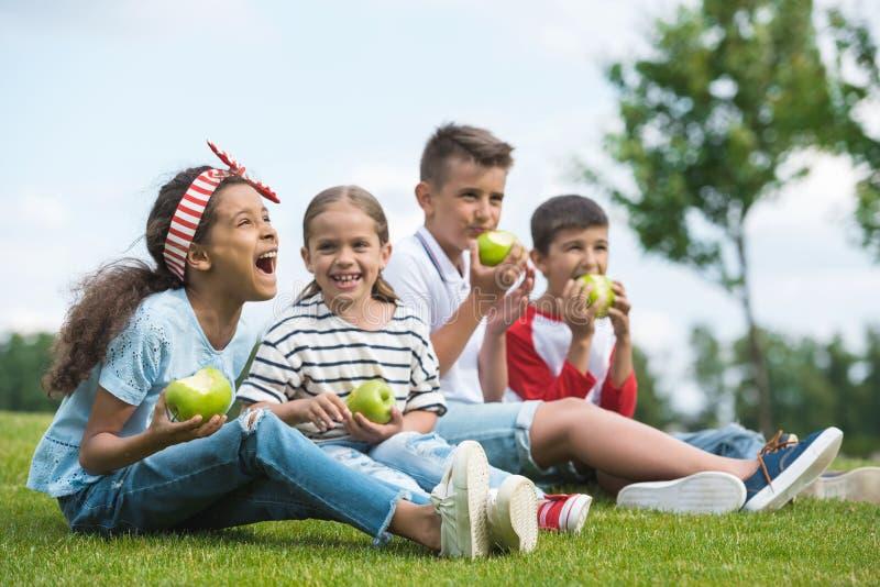 Niños multiétnicos que comen manzanas verdes mientras que se sienta junto en hierba verde fotografía de archivo libre de regalías