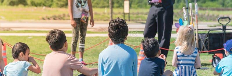 Niños multiculturales de la vista posterior panorámica del primer en prado de la hierba del juego al aire libre fotos de archivo libres de regalías