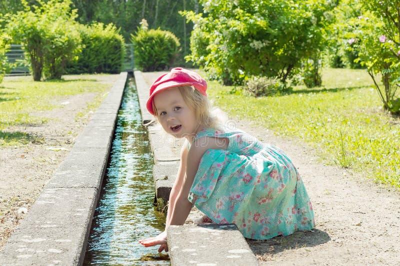 Niños Niña que juega con agua en una cala en un día soleado caliente fotografía de archivo