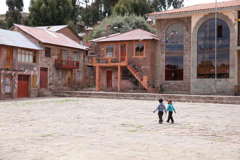 Niños no identificados en la isla de Taquile Su situado en el lago Titicaca, 45 kilómetros a poca distancia de la costa de la ciu imagenes de archivo