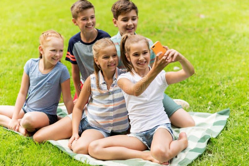 Niños o amigos felices que toman el selfie en parque del verano fotografía de archivo