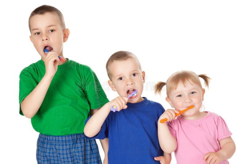 Niños para aplicar sus dientes con brocha imagen de archivo libre de regalías