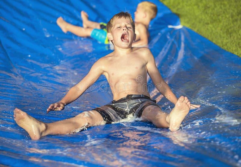 Niños pequeños emocionados que juegan en un resbalón y una diapositiva al aire libre fotografía de archivo libre de regalías