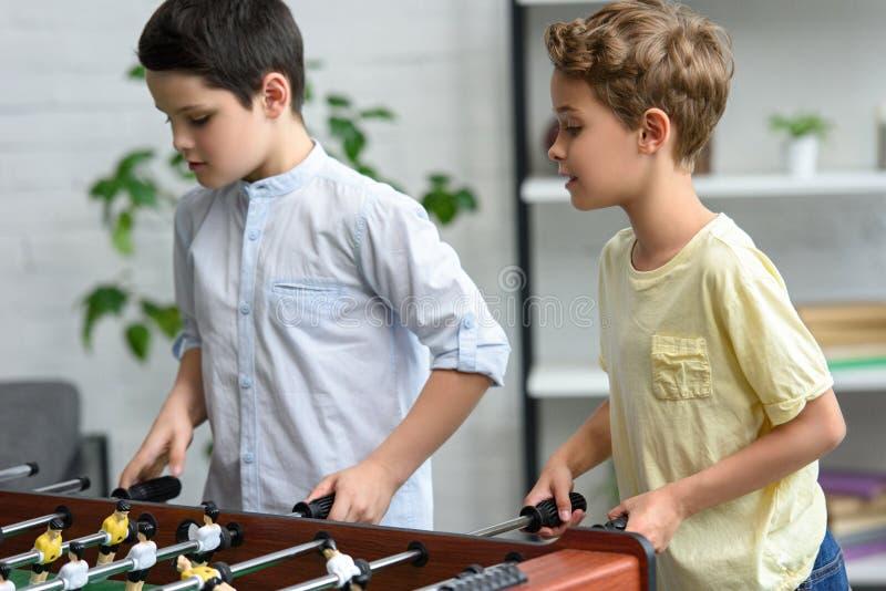 niños pequeños enfocados que juegan al fútbol de la tabla junto fotos de archivo