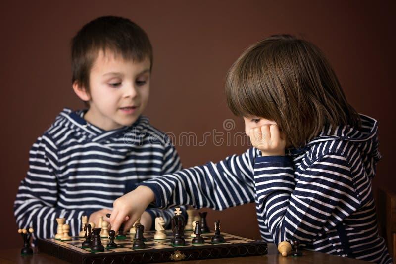 Niños pequeños, jugando a ajedrez Niño elegante, jugando al ajedrez a imagen de archivo