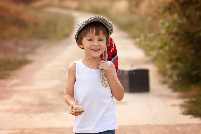 Niños pequeños lindos, sosteniendo un paquete, comiendo el pan y sonriendo, wa imagenes de archivo