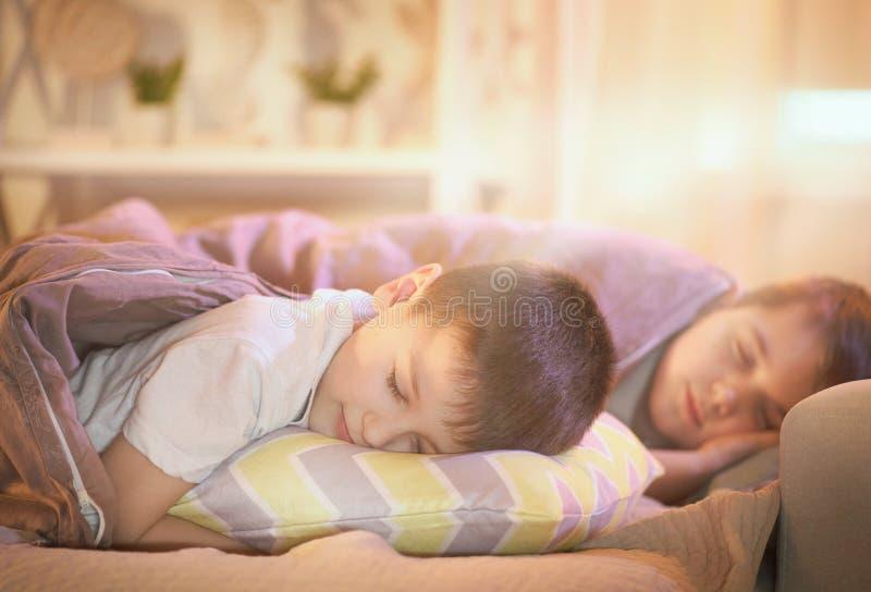 Niños pequeños que duermen en una cama, cubierta con una manta foto de archivo