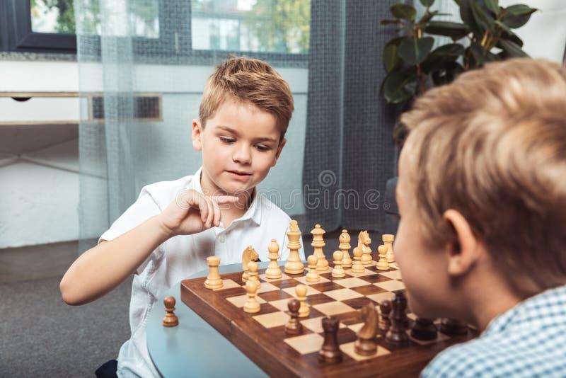 niños pequeños que juegan a ajedrez imagen de archivo