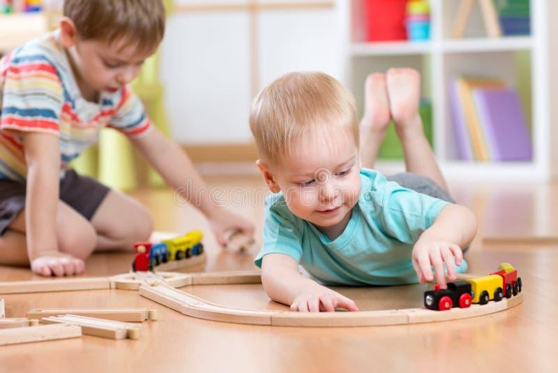 Niños pequeños que juegan con el sistema de madera del tren fotografía de archivo libre de regalías