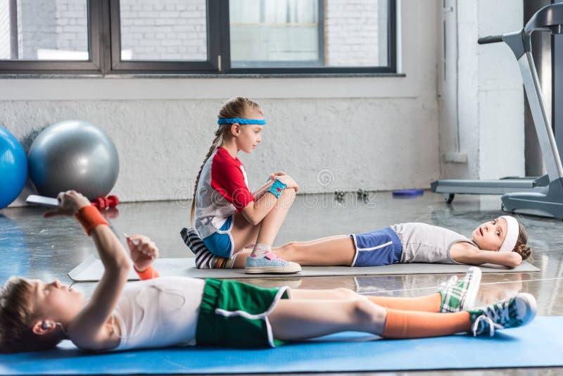 Niños pequeños que mienten en la estera de la yoga y que usan smartphone mientras que amigos que ejercitan en gimnasio imagenes de archivo