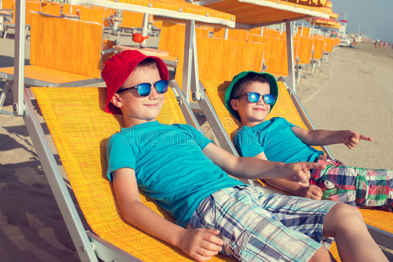 Niños pequeños que muestran lejos en deckchair en la playa imágenes de archivo libres de regalías