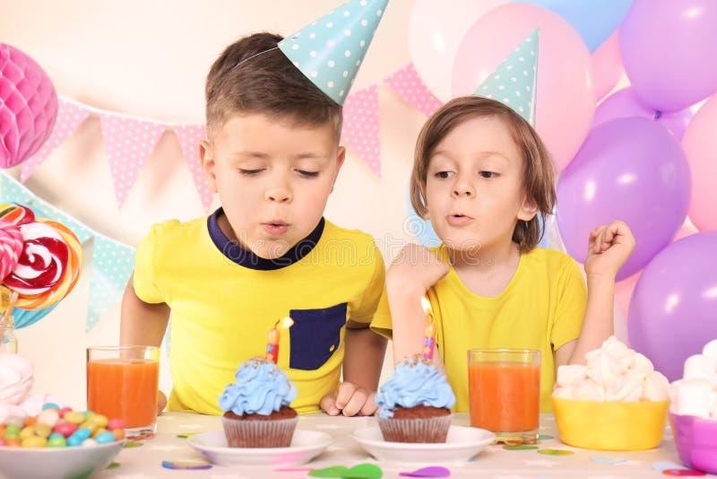 Niños pequeños que soplan hacia fuera velas en las magdalenas del cumpleaños en casa imagenes de archivo