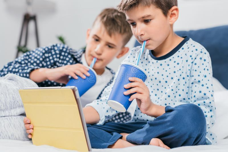 niños pequeños que usan la tableta y bebiendo soda mientras que miente en cama foto de archivo