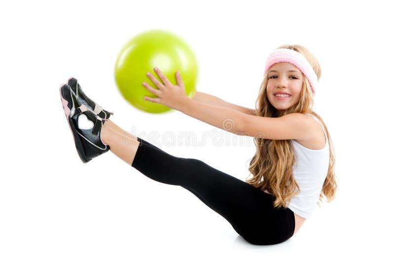 Niños poca muchacha de la gimnasia con la bola verde de la yoga imagenes de archivo