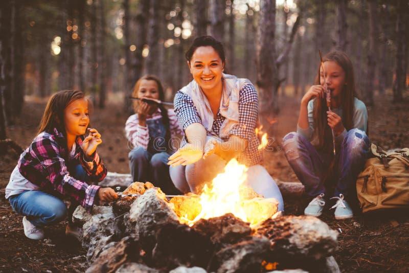 Niños por el fuego en bosque del otoño foto de archivo libre de regalías