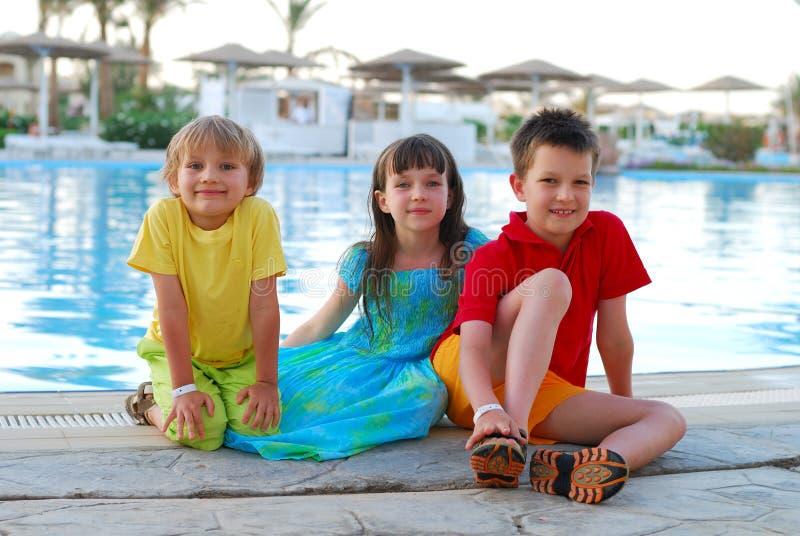 Niños por la piscina imagen de archivo libre de regalías