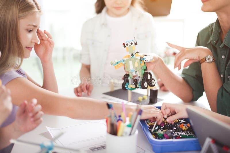 Niños positivos que crean el juguete durante la lección foto de archivo