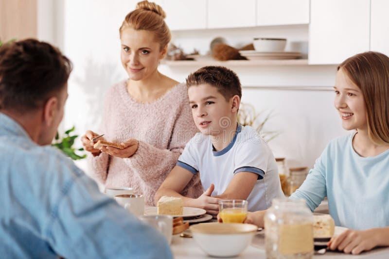 Niños positivos que desayunan con sus padres imágenes de archivo libres de regalías