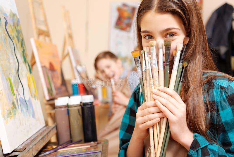 Niños positivos que se divierten durante la lección de la pintura imagen de archivo libre de regalías
