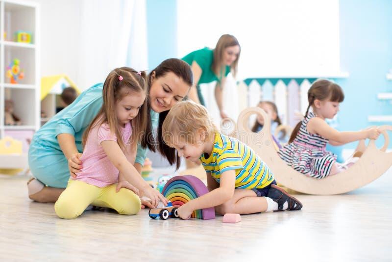 Niños preescolares que juegan con el profesor en guardería foto de archivo
